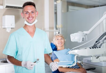 Confident male dentist standing in dental office with female patient in chair