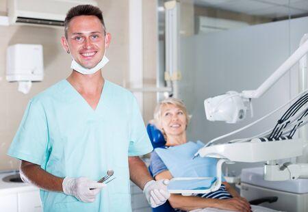 Dentista masculino seguro de pie en el consultorio dental con paciente en silla