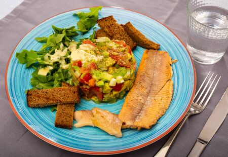 Image of tasty salad guacamole with arugula and tomatoes aerved with grilled trout fillet at plate