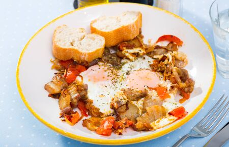 Hearty breakfast of eggs fried with pork meat and sliced tomatoes seasoned with dried herbs served with bread