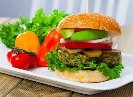 Appetizing vegetarian burger with grilled vegetable cutlet, fresh lettuce, tomatoes, onion, pickled cucumbers and avocado on white plate Stock Photo