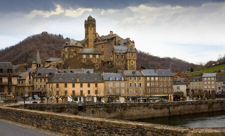 Scenic landscape of French village of Estaing on bank of Lot river with medieval Chateau in cloudy winter day Redactioneel