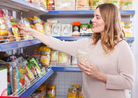 Portrait of positive female choosing groats in grocery food store Stock Photo