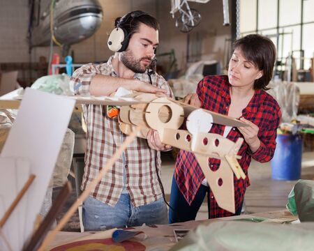 Female and male hobbyists engaged in creating plane models in aircraft workshop Stock Photo