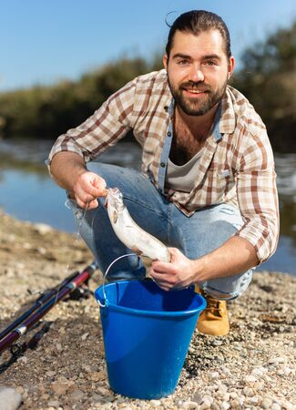 Adult male fisherman holding fish in his hands