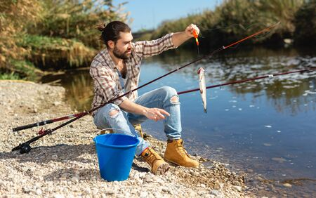 Bearded adult man posing with fish near river in summertime
