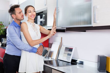 Young smiling couple choosing material for facades for their future kitchen Stok Fotoğraf