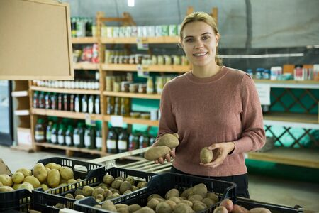 Cheerful woman choosing potatoes among different varieties in market shop Stock Photo