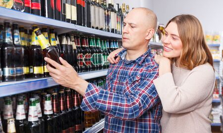 Portrait of family couple buying bottle of alcohol drink in a supermarket