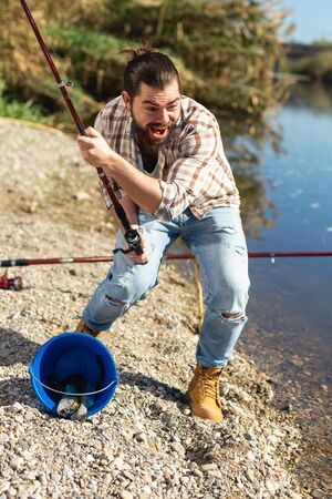 Happy fisherman pulls fish out of the river Reklamní fotografie