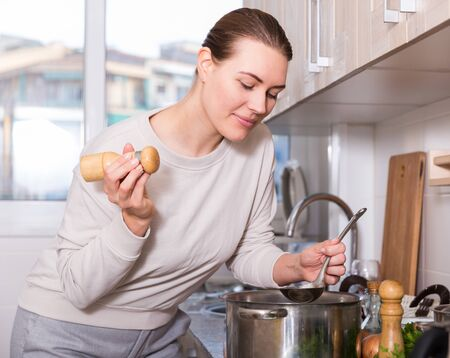 Young woman is cooking soup and salt it in the kitchen at the home.