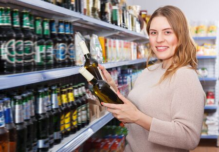 Portrait of pretty woman customer buying bottle of wine in the supermarket