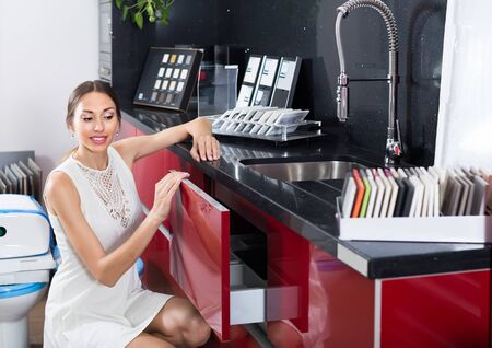 cheerful woman selecting modern kitchen furniture
