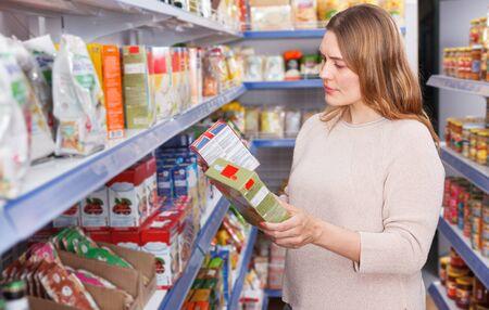 Portrait of woman customer choosing groats at grocery food shop