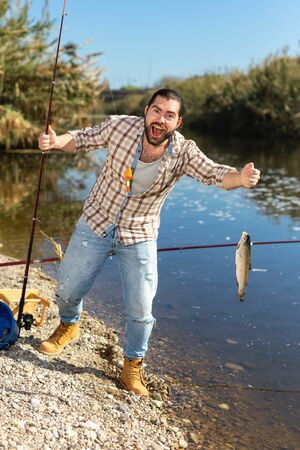 Adult man standing near river and pulling fish expressing emotions of dedication Reklamní fotografie