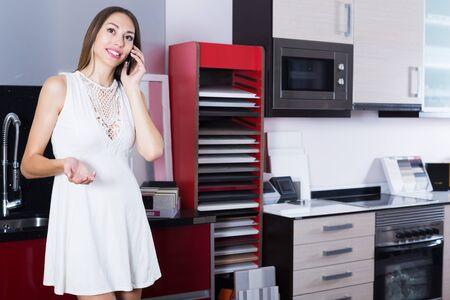 Smiling woman having phone conversation in kitchen furniture salon