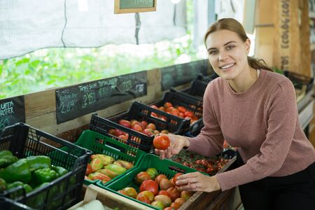Smiling young woman choosing tomatoes in grocery store Stock Photo