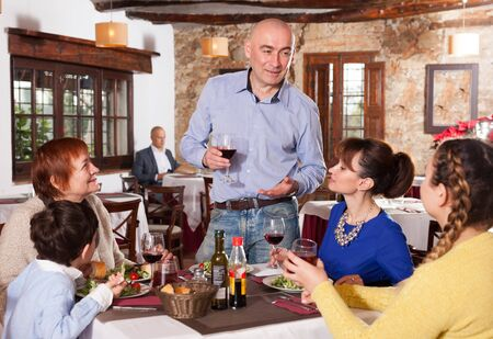 Happy man standing with glass of wine and saying his toast to his family at restaurant