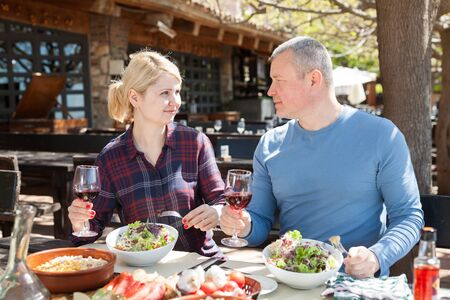 Family couple enjoying warm spring day and delicious dinner with wine in cosy country restaurant in open air