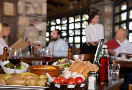 Closeup of served table with traditional dishes and wine in cozy rustic restaurant