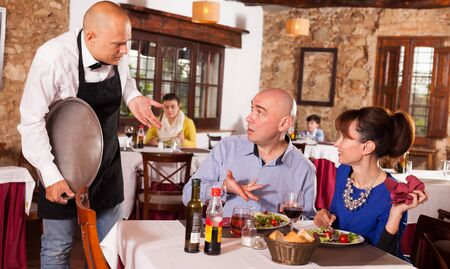 Outraged man and woman unhappy with quality of food in restaurant