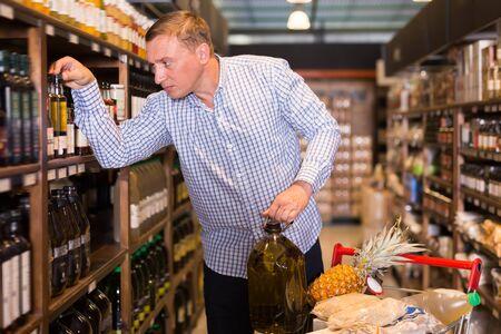 Glad male customer choosing olive oil in supermarket