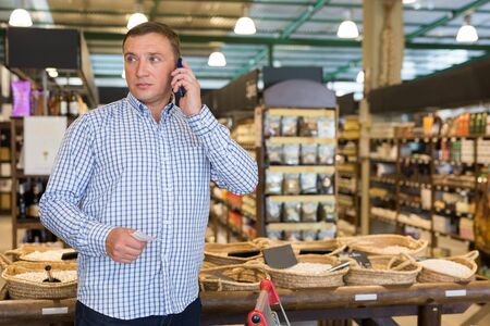 Portrait of man holding shopping list and talking on smartphone in supermarket Stock Photo