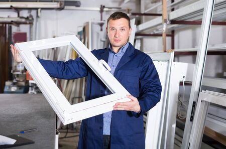 Handsome labour demonstrating finished PVC profiles and windows at factory