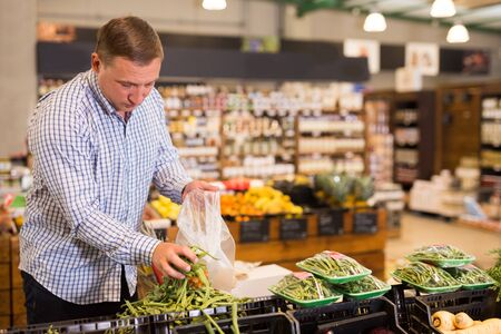 Portrait of man choosing green beans in supermarket