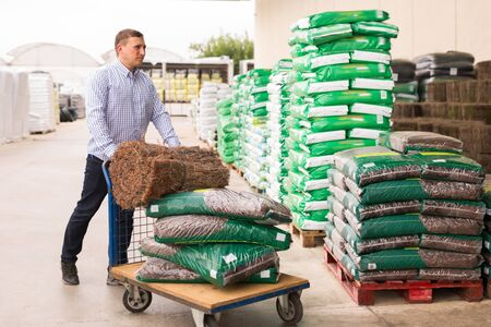 Active male buying compost soil for gardening in hypermarket Stock Photo