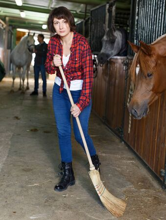 Young female worker sweeping floor at horse stable