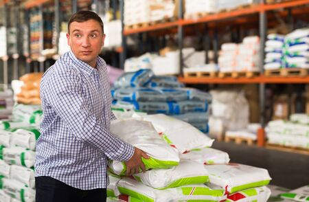 Adult man buying compost soil for gardening in hypermarket Stock Photo