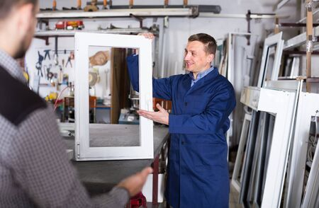 Production happy european worker in coverall demonstrating different PVC windows to customer