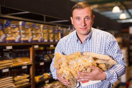Portrait of adult man buying pasta in supermarket