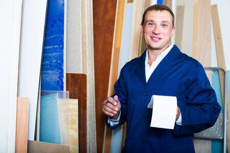 portrait of positive man in uniform choosing compressed densified wood in picture framing atelier