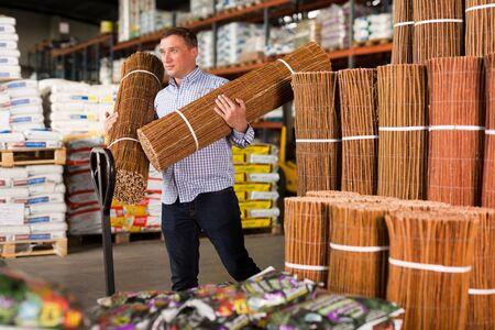 Man choosing bamboo fence for garden in hypermarket