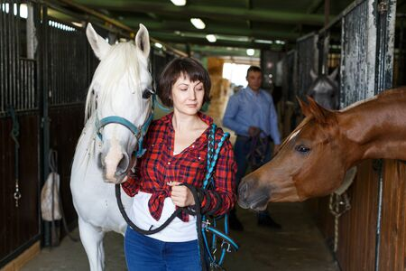 Portrait of woman farm worker standing at horse stable