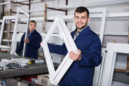 Smiling careful workman showing PVC manufacturing output in workshop