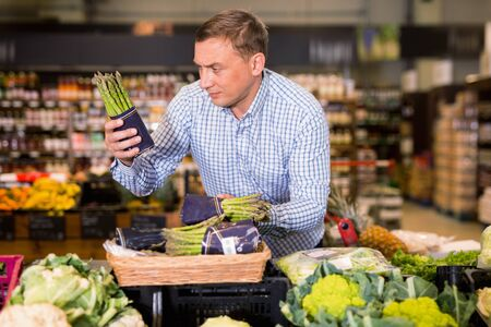 Portrait of glad cheerful  smiling man choosing asparagus in supermarket