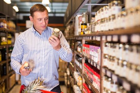 Portrait of male customer buying spices in supermarket