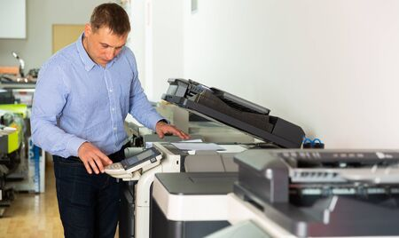 Confident businessman using printer in office Banque d'images