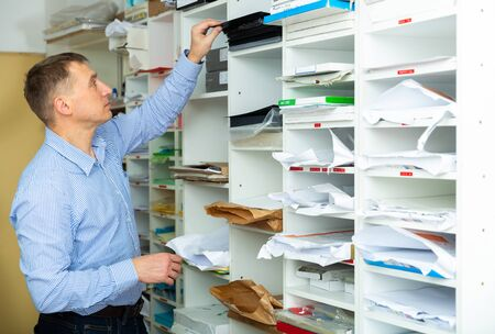 Office worker puts paper and printing film on the shelves