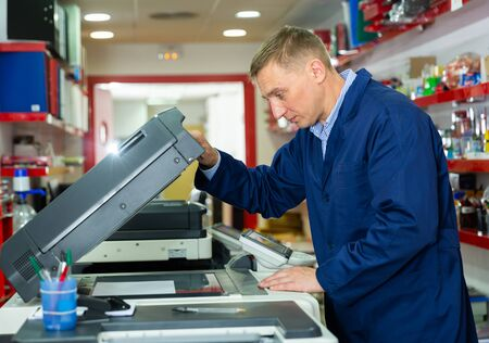 Portrait of confident service engineer standing by photocopy machine in office