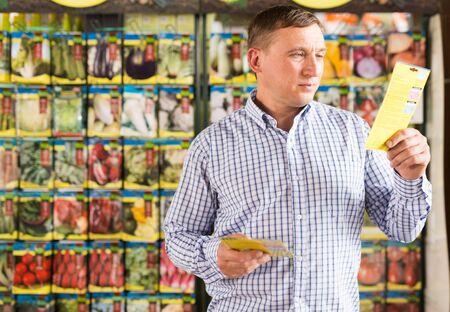 Portrait of man choosing vegetable seeds in supermarket Stock Photo