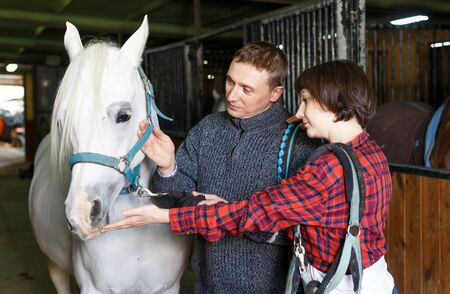 Happy man and woman in casual clothes at horse stable