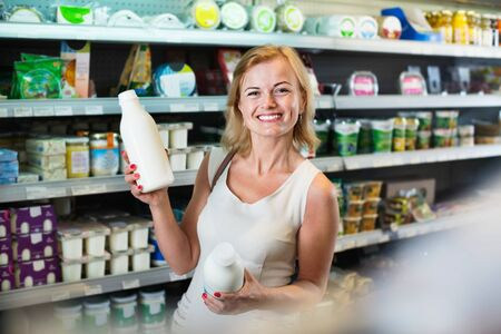 Portrait of smiling woman holding bottle with fresh milk in grocery shop