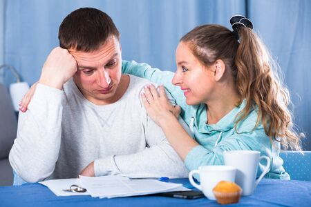 Middle-aged family struggling to pay utility bills and rent for their apartment