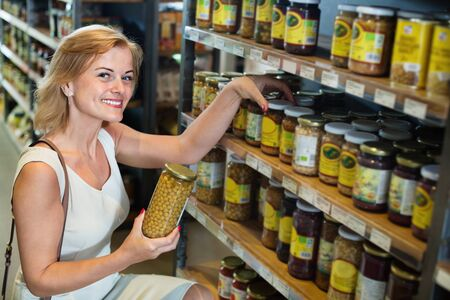 Portrait of happy positive smiling woman buying conserve peas in glass jar in grocery shop Stock Photo
