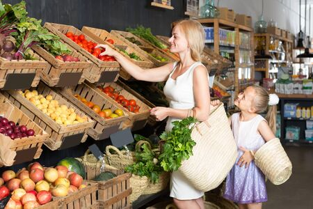 ?cheerful female customer with daughter near shelfs with vegetables in food shop