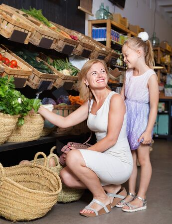 Glad young mother with pretty smiling daughter shopping various veggies in food store